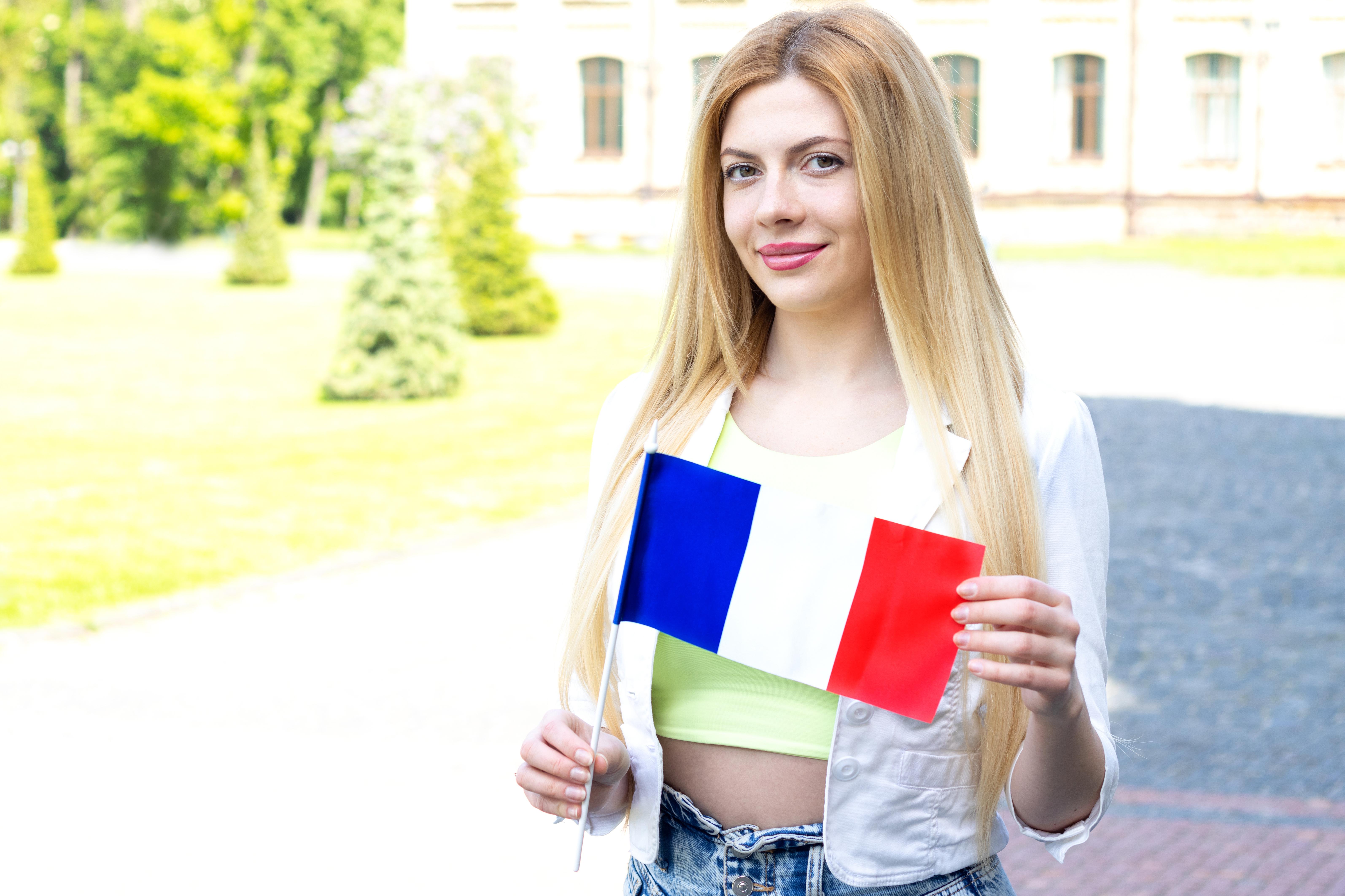 Девушка с флагом Франции, куда есть возможность переехать для беженцев