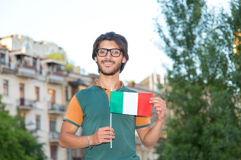 Парень с флагом Италии, куда есть возможность переехать для беженцев