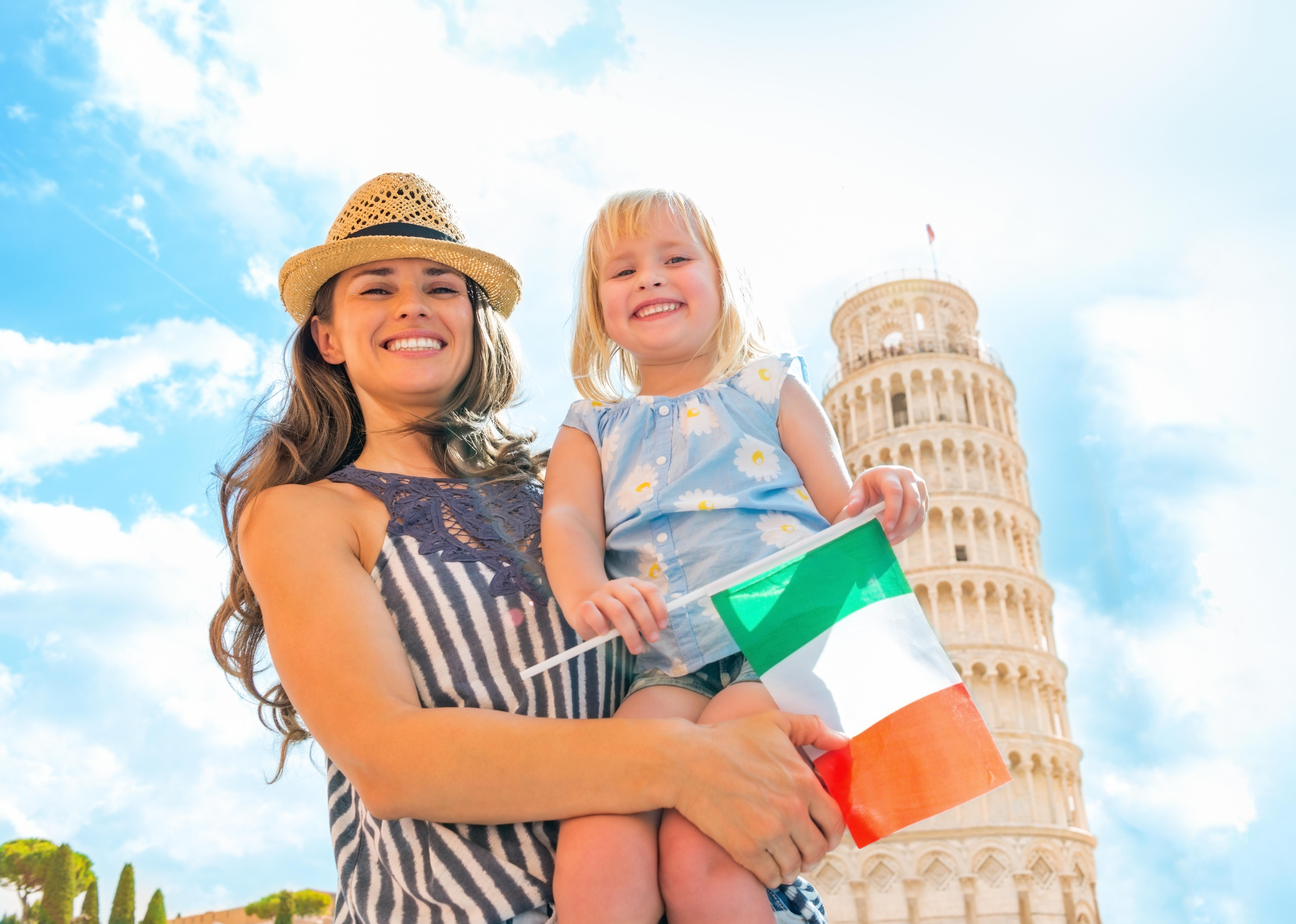 Мама с ребенком держат флаг Италии, ВНЖ которой можно получить для детей